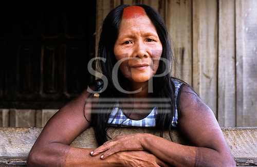 Bacaja village, Amazon, Brazil. Woman with shaved head, arms folded; Xicrin tribe.