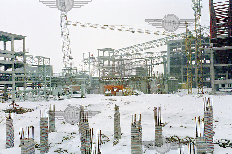 Construction workers assembling a crane on the construction site of a new coal-fired power station. China is in the process of building over 500 new coal power plants to meet the increasing energy demand.