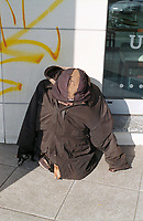 Milano, periferia nord. Un senzatetto rannicchiato a terra sotto al suo giubbotto --- Milan, north periphery. A homeless crouched on the ground under his jacket