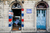 A Salvadoran hairdresser cuts a man's hair in a vintage barber shop in an unkept colonial house in San Salvador, El Salvador, 10 April 2018.