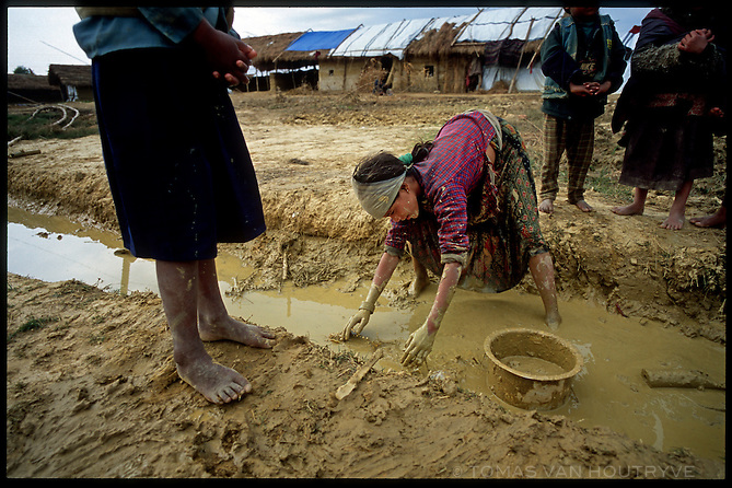 A refugee girl collects mud for house construction at the Kirin Khola Camp for internally displaced persons in Nepal on Monday, 7 February 2005. Families that have fled Maoist held areas are living in the camp.<br />