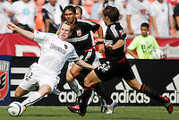 The MetroStars' Tim Regan looks to pass as he is double teamed by D.C. United's Jaime Moreno and Bobby Convey. D.C. United defeated the NY/NJ MetroStars 6 to 2 at RFK Stadium, Washington, D.C., on July 3, 2004.