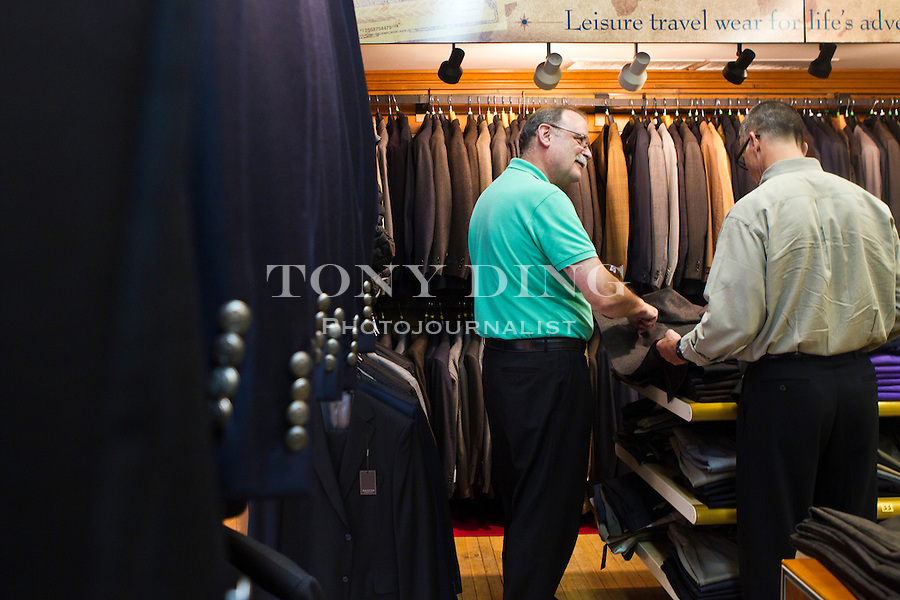 """""""Hank"""" of The Van Boven Shop, left, advises on shades of a sports jacket a father is looking for to gift his U of M son, Friday, Sept. 2, 2011 in Ann Arbor, Mich. (Tony Ding for The New York Times)"""