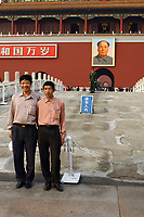 CHINA. Beijing.  Two men stand in front of the famous Mao Zedong portrait that hangs on the 'Gate of Heavenly Peace' which leads into the Forbidden City and is opposite Tiananmen Square. Mao is still revered in China even 30 years after his death and 40 years since the end of the 'Cultural Revolution' and the 'Great Leap Forward' where it is alleged he was responsible for the death of some 20 million Chinese people. Nevertheless, every day thousands of Chinese people make the pilgrimage to stand and have their photo taken in front of his most famous portrait. 2005.