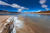 Salar de Aguas Calliente lagoon panorama with the Láscar Volcano under a blue sky, white clouds mirroring the ice, San Pedro de Atacama Chile