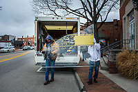 Workers remove a broken window from Cala Luna in Uptown Westerville.