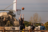 In a sign of waning COVID restrictions a group of young men play basketball at a neighborhood park in the San Francisco Bay area.