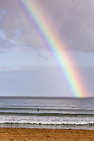 A morning surfer under a rainbow at Hanalei Bay, as seen from Hanalei Beach, Kaua'i.