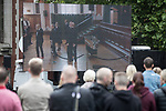 © Joel Goodman - 07973 332324 . 30/06/2017 . Stockport , UK . Mourners watch the service on a screen outside the Town Hall . The funeral of Martyn Hett at Stockport Town Hall . Martyn Hett was 29 years old when he was one of 22 people killed on 22 May 2017 in a murderous terrorist bombing committed by Salman Abedi, after an Ariana Grande concert at the Manchester Arena . Photo credit : Joel Goodman