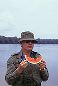 Amazon, Brazil. Tourist on the river bank eating a slice of watermelon wearing beanie hat carrying Swiss army knife and binoculars