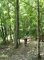 """SueEllen Novick cruises through the forest June 11 2021 on the Marble Flats trails minutes from downtown Eureka Springs. Novick samples the """"Beauty Is Everywhere"""" loop that guides riders past rock formations, a skills area and acres of woods.<br />(NWA Democrat-Gazette/Flip Putthoff)"""