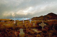 The historical Dos Cabezas Pioneer Cemetery with cross grave markers on a stormy day with a small 'sun dog' rainbow in the distance. Arizona.