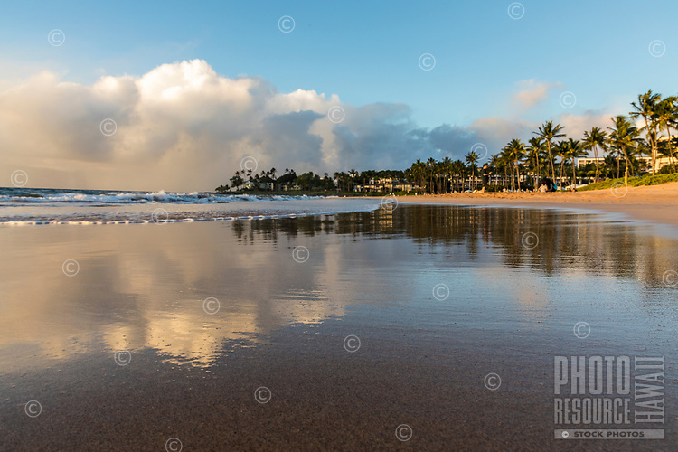 An afternoon scene at Maui's Wailea Beach is reflected in the peaceful water at its shoreline.