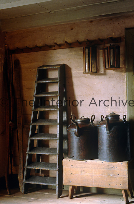 Two iron kettles stand on a bench and a ladder leans against the wall in this storage room