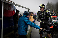 Luke Durbridge (AUS/Mitchelton-Scott) has trouble getting his rain jacket on and needing help from by-standers to get it on up the extremely wet, cold & misty Cole di Mortirolo <br /> <br /> Stage 16: Lovere to Ponte di Legno (194km)<br /> 102nd Giro d'Italia 2019<br /> <br /> ©kramon