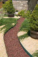 Path to house made of stone pebbles next to Abies evergreen trees in container pots, with contrasting colored stone mulch, stone house, ferns, barrel plantings , hostas in bloom, lambs ears