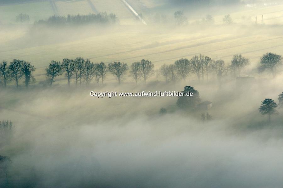 """4415/Nebel:DEUTSCHLAND, NIEDERSACHSEN 29.11.2003: Unter Nebel (althochdeutsch nebul über lateinisch nebula von griechisch nephele """"Wolke"""") versteht man in der Meteorologie fein verteilte Wassertröpfchen, die durch Kondensation in feuchtegesättigter Luft entstanden sind. Technisch gesehen ist Nebel ein Aerosol...Erst bei einer Sichtweite von weniger als einem Kilometer wird von Nebel gesprochen. Sichtweiten von einem bis vier Kilometern gelten als Dunst. Nebel wie Dunst unterscheiden sich von Wolken nur durch ihren Bodenkontakt, sind jedoch ansonsten nahezu identisch zu ihnen. Einen Nebel in räumlich sehr begrenzten Gebieten bezeichnet man als Nebelbank. Als Nebeltag bezeichnet man einen Tag, an dem mindestens einmal ein Nebel aufgetreten ist..Luftbild, Luftansicht, Baumreihe, Einzelne Haeuser im Nebel."""