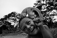 A Nukak boy plays with a baby monkey in a refugee camp close to San Jose del Guaviare, Colombia, 4 September 2009. The Nukak Maku people, nomadic hunter-gatherers from Amazonia, were violently driven out of the jungle by the Colombian guerilla and paramilitary squads. Now, roughly cut off their original tribal lifestyle, they stuck between worlds. They learn from the (mainly Christian) aid workers to use clothes, to listen to the radio, to beg for money. Although their digestion suffer, they love to eat sweets, cookies and other western food. They have hunted out all the animals around and now there is nothing left for them. Nukak can not return to the jungle, their world has already passed through an irreversible change.