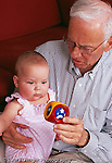 8 month old baby girl with grandfather interested in toy he holds vertical