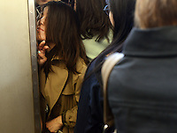 A passengers squeezes herself onto a train during morning rush hour, Shinjuku Station, Tokyo. With up to 4 million passengers passing through it every day, Shinjuku station, Tokyo, Japan, is the busiest train station in the world. The station was used by an average of 3.64 million people per day.  That's 1.3 billion a year.  Or a fifth of humanity. Shinjuku has 36 platforms, and connects 12 different subway and railway lines.  Morning rush hour is pandemonium with all trains 200% full. <br /> <br /> Photo by Richard jones / sinopix