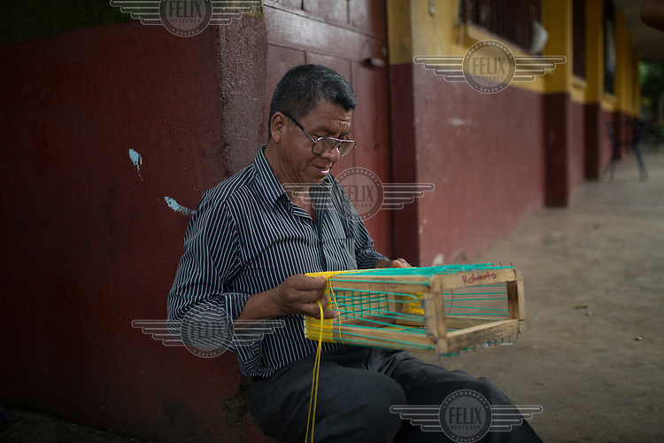 War survivor Roberto Gonzalez, 52, weaves a plastic basket at the Jose Marti Federation school, current shelter for the Fuego Volcano-affected community members from La Trinidad. A local Rotay Club-sponsored techincal school has been teaching community members affected by the Fuego volcano how to weave the baskets in order to create some income. Each basket takes about a day's work and sells for roughly USD8. Originally from Huehuetenango, hundreds of families fled to Mexico in 1982 escaping state-repression during the war. In 1998, after the peace accords, the families were given land at the foot of the Fuego Volcano as part of an agreement for returning refugees. Today, La Trinidad is one of the most affected communities due to the 3 June 2018 eruption. Their community has been deemed uninhabitable and the 235 families await an uncertain future once again.