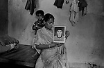 Sunita Devi wife of Late Santraj Prasad(who died in Bagdigi mine accident on 2.2.2001 at 11.15 am where 26 other miners killed) at her home with her husbands photograph and her younger child. Jharia, Jharkhand, India. Arindam Mukherjee
