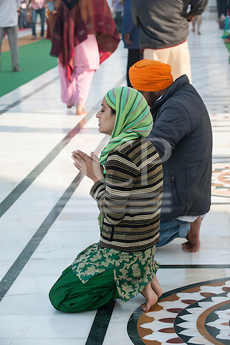 Amritsar, Punjab, India. A man and a woman praying on their knees at the Golden Temple.