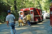 Firefighters and paramedics load a victim into the ambulance after a vehicle accident in Occidental California