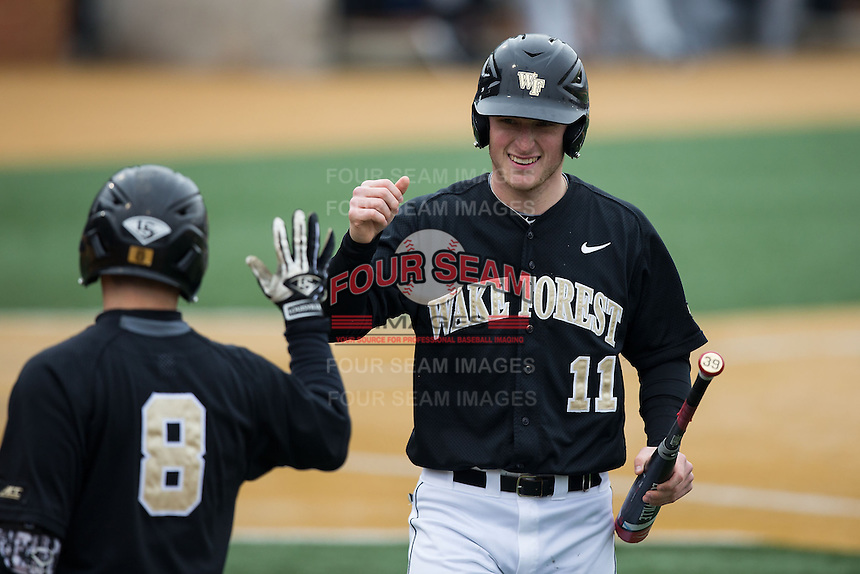 Jonathan Pryor (11) of the Wake Forest Demon Deacons fist bumps with teammate Joey Rodriguez (8) after scoring a run against the Towson Tigers at Wake Forest Baseball Park on March 1, 2015 in Winston-Salem, North Carolina.  The Demon Deacons defeated the Tigers 15-8.  (Brian Westerholt/Four Seam Images)