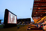Notts County 150th Anniversary, 18/11/2012. Meadow Lane. Spectators in the Derek Pavis stand watching a film entitled 'Notts County - the Movie' on an inflatable screen at Meadow Lane, home of Notts County FC during a special Legends Day event marking the club's 150th anniversary. The day-long event featured autograph signing by past and present players, a game between two teams of former players and the film screening. The club were founder members of the Football League in England and call themselves 'the world's oldest Football League club'. Photo by Colin McPherson.