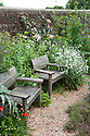 Seating area in upper garden, Fairlight End, Pett, East Sussex, late June.