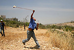 A Palestinian boy hurls a stone at Israeli soldiers during a demonstration against Israel's controversial separation barrier in the West Bank village of Nilin, near Ramallah. Five Palestinians were wounded today as Israeli soldiers fired rubber bullets at demonstrators protesting at the construction of a separation wall on the outskirts of Nilin, medics said.