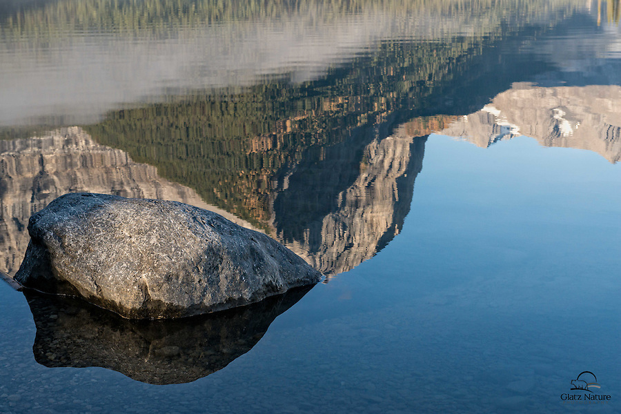 Partially submerged rock fits right into the reflection.  Upper Kananaskis Lake, Peter Lougheed Provincial Park, Alberta, Canada.