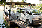 A van crossing a river on a wooden ferry on the road to Xunantunich in the Cayo District in in Belize