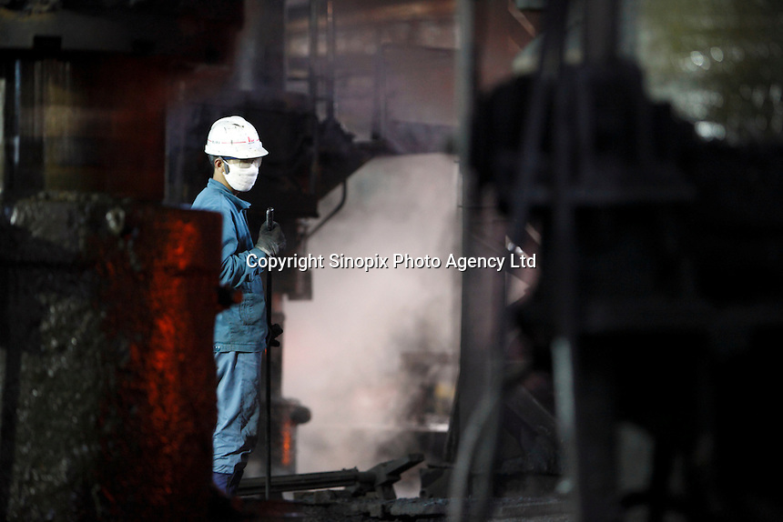 Workers operate on the old assembly line that was built in the 1960s to make train carriage wheels at Ma Steel in Maanshan, China. With an additional plant that opened last year, Ma Steel is the world's largest producer of train carriage wheels with an annual capacity of 1.1 million units..29 Dec 2008.