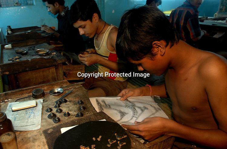 A young gold factory worker studies a sketch of an ornament before starting his days work. Kolkata, India  6/13/2007  Arindam Mukherjee