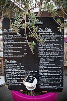 The menu board leans on an olive tree at Achill's restaurant, Villefranche-sur-Mer, France, 7 September 2012.