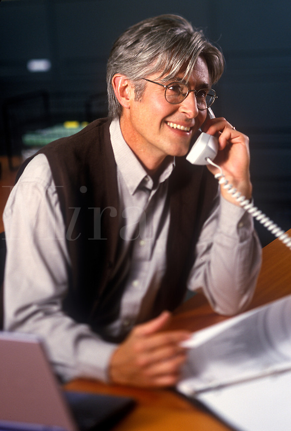 Smiling man on office phone.