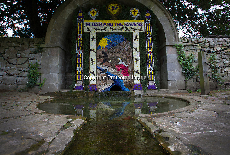 14/05/15<br /> <br /> Hall Well - the village's main well situated opposite Tissington Hall. This year showing a Biblical design based on Elijah and the Ravens.<br /> <br /> To mark ascension day this year's well dressings are unveiled and blessed by the local clergy in the Derbyshire village of Tissington in the Peak District National Park.<br /> <br /> Before today's blessings, wooden boards coated in clay are decorated with tens of thousands of petals, leaves and pieces of foliage to create the giant intricate mosaics. The boards,  take teams of many villagers three days to make. <br /> <br /> The village has been decorating its six wells every year for more than six hundred years. The tradition is believed to be a celebration of the wells never running dry, giving life and  sustaining the village during times of plague. After a church service today (Thursday)  clergy from six parish will bless each of the well.  <br /> <br /> Following in Tissington's footsteps many other villages in the Derbyshire area also have their own well dressing traditions.<br /> <br /> <br /> All Rights Reserved: F Stop Press Ltd. +44(0)1335 418629   www.fstoppress.com.