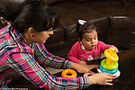 12 month old baby girl exploring new stacking ring toy, mother holding base to facilitate pulling off the rings