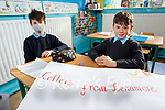 Matthew St John and Sean Scanlon Kennelly writing their letters to people in the community on Monday.
