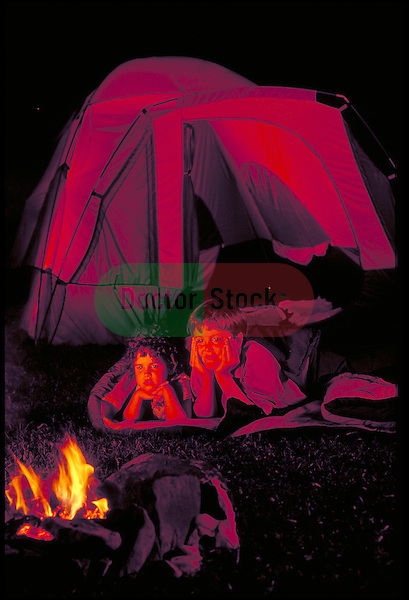 children camping watching campfire from sleeping bags