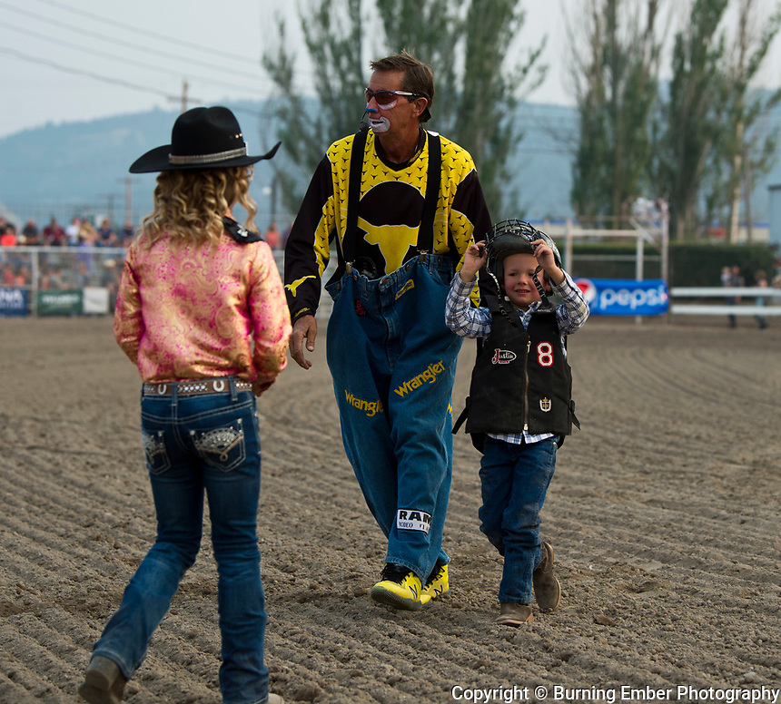 Dennis Halstead walks a young man off of the grounds after he takes a digger during the Mutton Bustin event at Northwest Montana Fair and  Rodeo Kalispell MT August 18th, 2018.  Photo by Josh Homer/Burning Ember Photography.  Photo credit must be given on all uses.