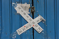 Paper strips seal the closed factory warehouse door belonging to Smart Union, one of several factories in Zhang Mutou in South China that went bankrupt in the current credit crisis. Smart Union, that produced toys for Mattel amongst others, left 6,000 workers jobless and penniless after they could not pay the salaries. Hundreds of factories in south China are closing due to increased labor and material costs and the current credit crissis is exasperating. The problem leaving ghost towns behind. .24 Oct 2008