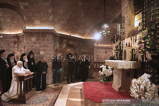 """Pope Benedict XVI is flanked by leaders of various religions as he prays in the Tomb of San Francesco in Assisi, during the day the 25th Interreligious talks, a """"journey of reflection, dialogue and prayer for peace and justice in the world"""" held in St. Francis of Assisi's birthplace,  October 27, 2011 in Assisi.Italy"""