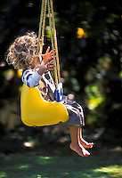 """Young girl swinging with """""""" no hands"""