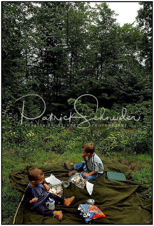 Two young boys share a picnic in the woods. Model released photo.