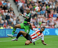 Jermain Lens of Sunderland flies in with a challenge on Andre Ayew of Swansea City during the Barclays Premier League match between Sunderland and Swansea City played at Stadium of Light, Sunderland