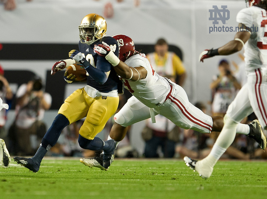 Jan. 7, 2013; Running back Cierre Wood gains yardage as Alabama linebacker Ed Stinson moves in for the tackle during the first quarter of the 2013 BCS National Championship in Miami, Florida. Photo by Barbara Johnston/University of Notre Dame