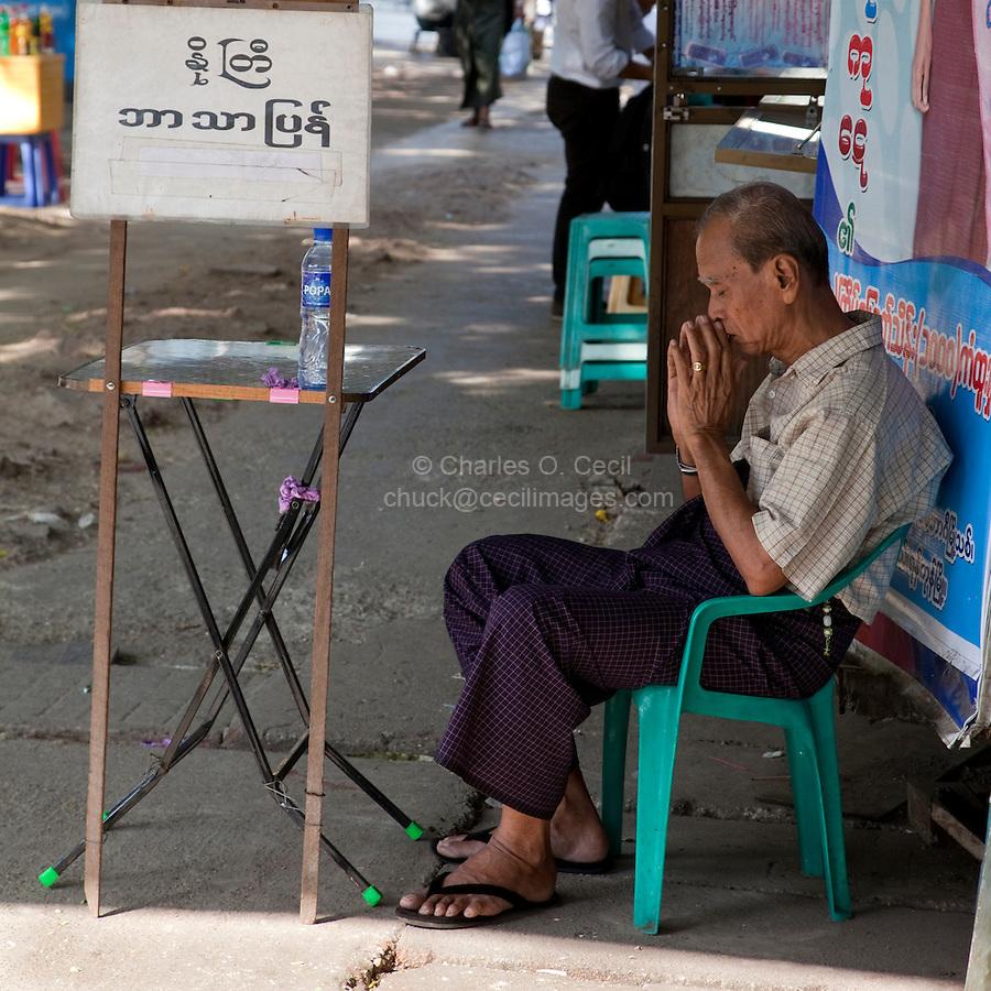 Myanmar, Burma, Yangon.  Man Sitting, Dozing, Possibly Praying, on Sidewalk.